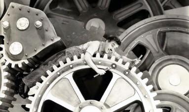 """Charlie Chaplin in una sequenza del celebre film """"Tempi Moderni"""", del 1936. è proprio nei primi decenni del secolo scorso che ci si è iniziati ad interrogare sulle conseguenze del rapporto fra l'uomo e la tecnologia. Fin da allora infatti si sottolineava come lo sviluppo tecnologico ed industriale andasse a creare un mondo dai ritmi molto più veloci e coinvolgenti, fino a rischiare di arrivare al punto di venir """"risucchiati"""" dalle macchine, come nel film di Chaplin, piccolo operaio incastrato fra gli ingrranaggi della catena di montaggio."""