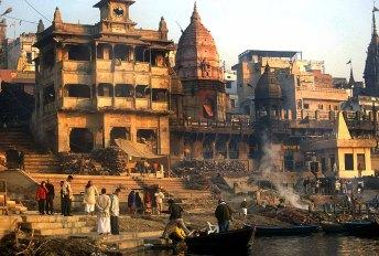 """Varanasi, Manikarnika Ghat. Il Ghat, che possiamo considerare come una specie di """"molo"""" sul fiume, è il luogo sacro nel quale vengono fatte le abluzioni rituali e bruciati i corpi. Il Manikarnika Ghat di Varanasi è il luogo dove vengono cremati i defunti, in mezzo al rumore di chi spacca e prepara la legna per i roghi, le campane e i canti sacri dei templi di Shiva, il via vai continuo delle persone. A rendere ancor più suggestivo e funereo il luogo è il colore dei palazzi, anneriti dai fumi dei roghi e circondati dagli indiani che bevono il the, discutono ed osservano la scena. Su tutto ciò regna un clima surreale dove la morte viene vissuta (almeno dalla popolazione locale) come un evento naturale e da vivere con serenità."""